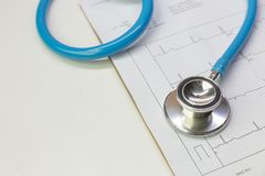 Blue stethoscopes and  Electrocardiography  chart close up image. A Blue stethoscopes and  Electrocardiography  chart close up image stock photos
