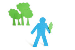 A blue stick figure holding a leaf representing concept of nature perseverance over white background stock images