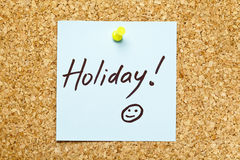 Blue sticky note 'Holiday!'. Blue sticky note on an office cork bulletin board with 'Holiday!' on it Stock Image