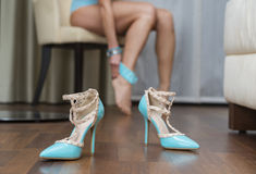 Blue stiletto high heels shoes, in the background woman with sto Royalty Free Stock Image
