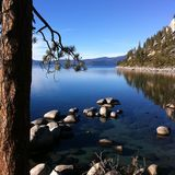 Blue Stillness. High contrast clouds and Lake with rock point. Lake Tahoe Nevada stock photo