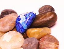 Blue stone. Picture of a blue polished stone in a pile of plain stones Stock Image