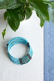 Blue stone beads necklace on white- blue background with plants Royalty Free Stock Image