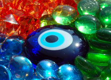 Blue stone eye on coloured glass stones. Nice coloured translucent glass stone on coloured glass pattern Royalty Free Stock Photo