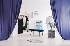 Sophisticated dressing-room with blue curtains. Blue stool next to designer table with flowers in sophisticated dressing-room with blue curtains Stock Image