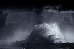 Blue storm. Big storm wave against lighthouse of Vila do Conde, north of Portugal (enhanced sky), at sunset - Black and White toned blue Stock Image
