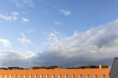 Blue stormy landscape sky on a building roof facade stock image
