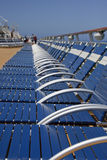 Blue Strap Chaise Lounges on Ships Deck. A row of blue plastic strap chaise lounges disappearing into the distance on the deck of a Cruise ship stock image