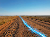 Blue streak of light on dirt road against clear sky Royalty Free Stock Photos