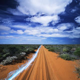 Blue streak of light on dirt road against cloudy sky Royalty Free Stock Photography