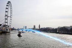 Blue streak of light passing over river Thames Royalty Free Stock Photography