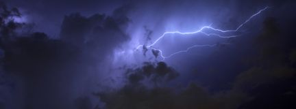 Blue Strike. Blue Lightning strike surrounded by storm clouds and rain columns Royalty Free Stock Images
