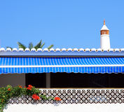Blue striped awning. A blue striped awning casting shade against a blue sky with a line of roof tiles and a whitewashed decorative wall with bougainvillea stock photo