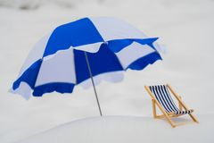 Blue striped chaise longue in the snow. Blue striped canopy next to a blue chaise longue in the snow stock images