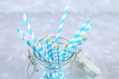Blue striped paper disposable tubes in a jar on a gray background. Blue striped paper disposable tubes in a jar on a gray background Royalty Free Stock Photo