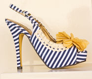 Blue striped shoe with cream bow. Royalty Free Stock Images