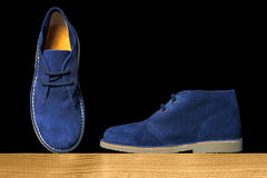 Blue suede boots. On a wooden shelf over a black background Stock Image