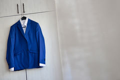 Blue suit hanged. To a wood closet in natural light Royalty Free Stock Image