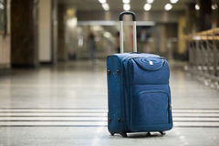 Blue suitcase at airport. Large blue wheeled suitcase standing on the floor in modern airport terminal. Copy space stock photo
