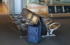 Blue suitcase at an airport lobby. Royalty Free Stock Photo