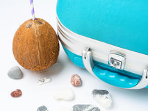 Blue suitcase, coconut and sea stones Stock Image