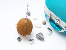 Blue suitcase, coconut and sea stones Royalty Free Stock Image