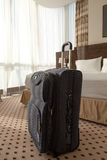 Blue suitcase in the hotel room. Large blue wheeled suitcase standing on the floor in the hotel room. Vertical image Royalty Free Stock Images