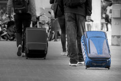 Blue Suitcase with tourist. Black and white background. Royalty Free Stock Images