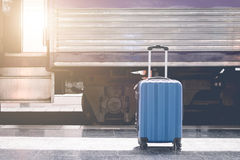 Blue suitcase at the train station with abstract light in retro. Effect. travel waiting concept stock photos