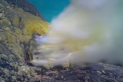 Blue sulfur flames and Sulfur fumes from the crater of Kawah Ijen Volcano in Indonesia.  stock photos