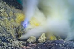 Blue sulfur flames and Sulfur fumes from the crater of Kawah Ijen Volcano in Indonesia.  royalty free stock images