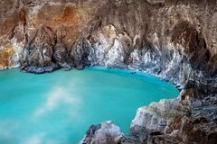 Blue sulfur toxic lake in the crater of the Ijen volcano. Poisonous sulfur smoke. Mountain volcanic landscape.  royalty free stock image