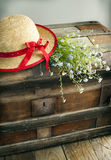 Blue summer flowers and straw hat on vintage chest Stock Photos