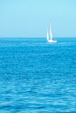 Blue summer seascape with distant yacht out of focus Stock Photos