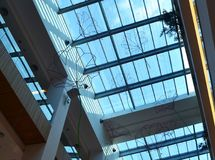 The blue summer sky and the glass roof of the shopping cente. R, the view from the bottom inside the building royalty free stock image