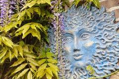 Blue sun face in garden Royalty Free Stock Image