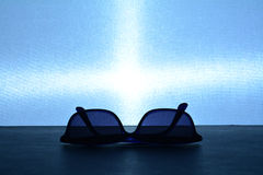 Blue sun glasses on a blue background. A backlight illuminates a pair of blue sunglasses on a blue background Royalty Free Stock Photos