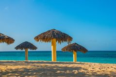 Umbrellas are on the beach, on the background of turquoise blue water. Playa Esmeralda, Holguin, Cuba. Blue sun loungers with umbrellas on the beach. On the royalty free stock photo
