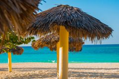 Umbrellas are on the beach, on the background of turquoise blue water. Playa Esmeralda, Holguin, Cuba. Blue sun loungers with umbrellas on the beach. On the stock photos
