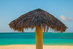 Umbrellas are on the beach, on the background of turquoise blue water. Playa Esmeralda, Holguin, Cuba. Blue sun loungers with umbrellas on the beach. On the royalty free stock photos