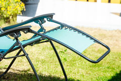 Blue sunbed deck chair in garden. Recreation and relaxation objects concept. Blue modern sunbed deck chair in garden Stock Photo