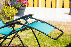 Blue sunbed deck chair in garden. Recreation and relaxation objects concept. Blue modern sunbed deck chair in garden Royalty Free Stock Image