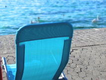 Blue sunbed. Sunbed by the water. Birds on the background Stock Image