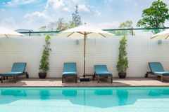 Blue sunbed with white umbrella by pool Royalty Free Stock Images