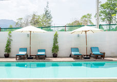 Blue sunbed with white umbrella by pool Stock Images