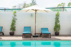 Blue sunbed with white umbrella by pool Royalty Free Stock Photos