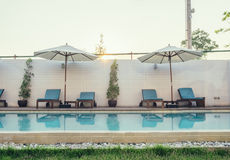 Blue sunbed with white umbrella on swimming pool. At sunset Royalty Free Stock Photos
