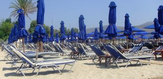 Blue sunbeds in the beach. A picture of blue sunbeds in a summer beach,in Athens,Greece,in a summer day of august Stock Photography