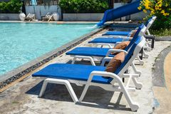 Blue sunbeds with mattress on side of swimming pool stock photos