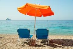 Blue sunbeds and orange umbrella (parasol) on Paradise Beach in stock photo